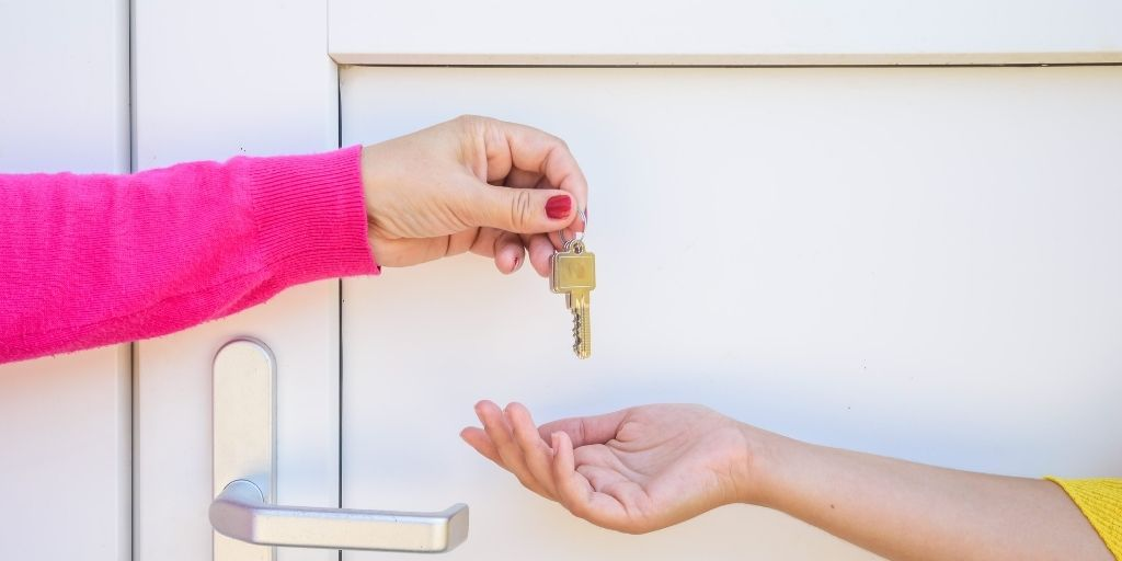 A lady gives another lady a set of home keys